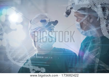 Panoramic view of helix pattern information on device screen against doctors looking at each other in operating room
