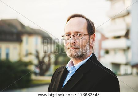 Outdoor portrait of 50 year old man wearing black coat and eyeglasses