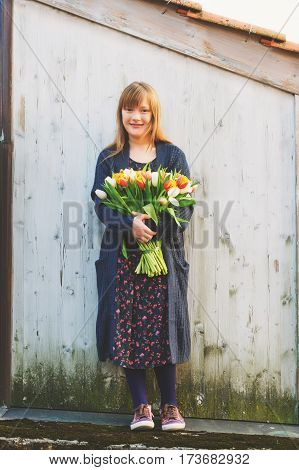 Portrait of cute 8-9 year old girl, holding bright bouquet of colorful fresh tulips, standing against white wooden background, wearing blue knitted jacket, long dress and modern shoes