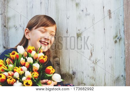 Portrait of cute 8-9 year old girl, holding bright bouquet of colorful fresh tulips, standing against white wooden background, laughing kid, eyes closed