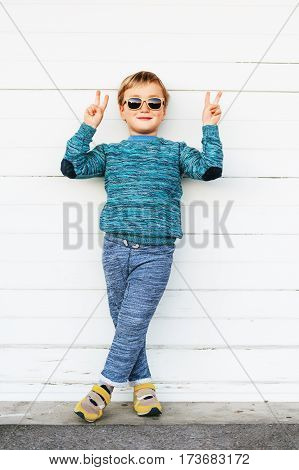 Fashion kid in sunglasses, wearing blue knitted pullover, joggers and yellow basket shoes, standing against white background, showing peace sign