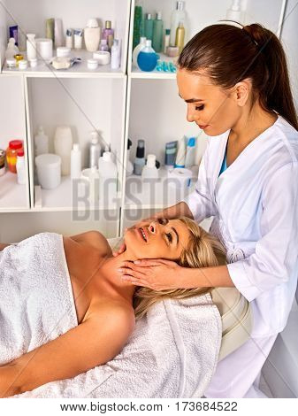 Spa and massage deals. Facial treatment for forty five year old woman . Portrait of woman middle-aged take face cleaning in European spa salon. Interior with cosmetic background.