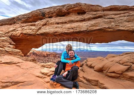 Happy friends hugging under the natural arch in Canyonlands National Park. Mesa Arch. Moab. Utah. United States.
