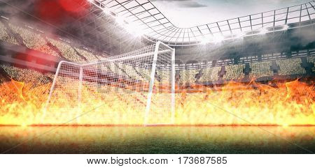 Large flames on black background against large football stadium with lights