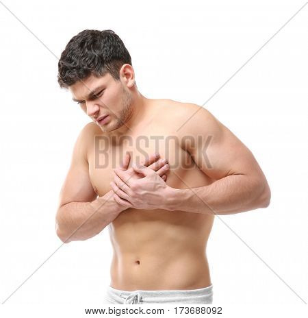 Handsome young man having heart attac on white background