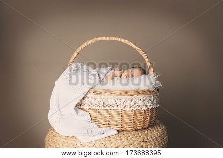 Cute little baby sleeping in wicker basket on color background