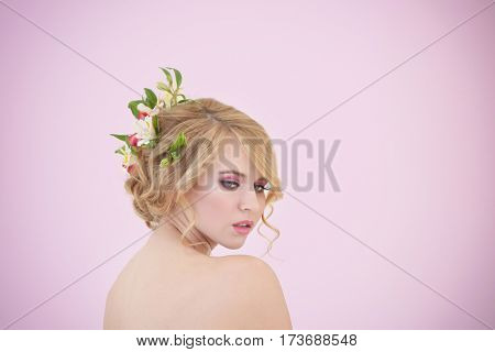 Beautiful young woman with flowers in hair on white background