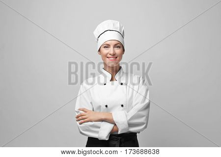 Portrait of female chef on light grey background