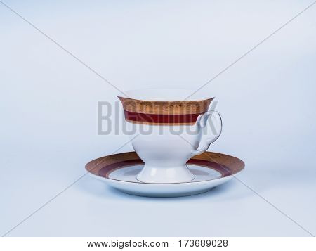 Close up white tea cup standing on saucer decorated with designs isolated on white background. Painting on a cup. Side view.