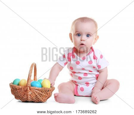 Cute funny baby with basket full of Easter eggs on white background