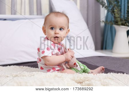Cute funny baby with bunny toy sitting on bed at home