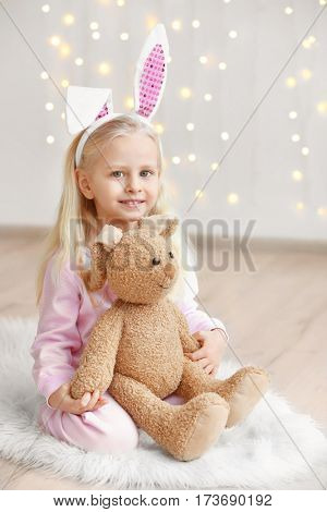 Cute funny girl with bunny ears and cuddly toy sitting on floor at home poster
