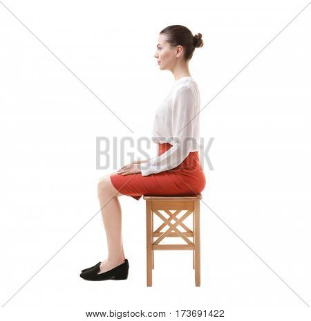 Incorrect posture concept. Young woman sitting on stool against white background