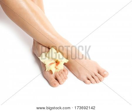 Female legs with flower on white background