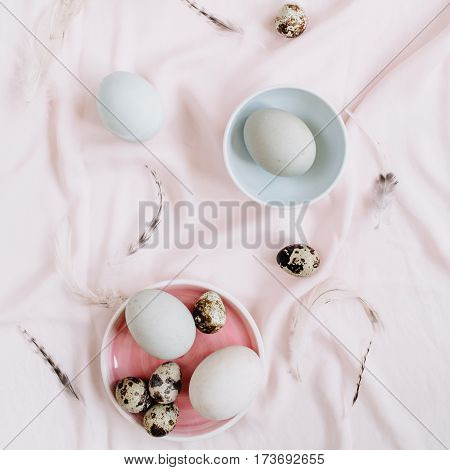 White Easter eggs quail eggs and feathers on pink textile background. Flat lay top view. Traditional spring concept. Easter concept.