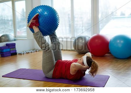 Side view portrait of determined overweight woman working out in fitness studio: performing straight leg sit ups with fitness ball on yoga mat