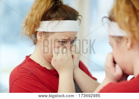Portrait of young overweight woman crying while looking in mirror, upset and dissatisfied with her body image