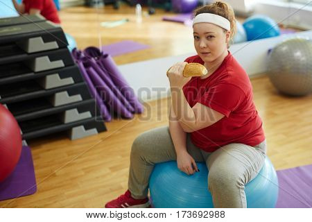 Portrait of beautiful plump woman working out in fitness studio: doing weightlifting exercises with sesame bun, sitting on big ball