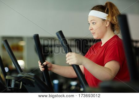 Side view portrait of determined overweight woman working out in gym: using ellipse machine with effort to lose weight