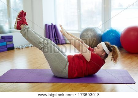 Side view portrait of determined obese woman working out in fitness studio: performing toe tap straight leg sit ups on yoga mat
