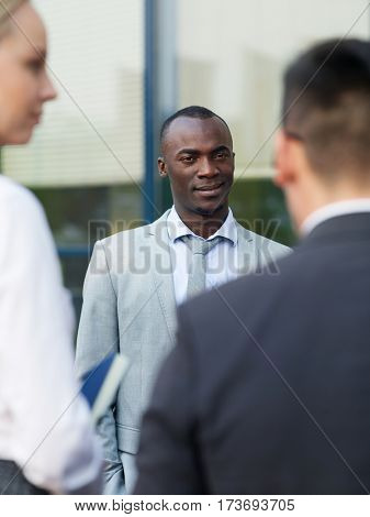 African-american man in formalwear talking to his co-workers