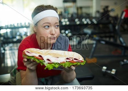 Portrait of cute overweight woman looking away from huge fat sandwich while working out in gym, struggling to keep fit