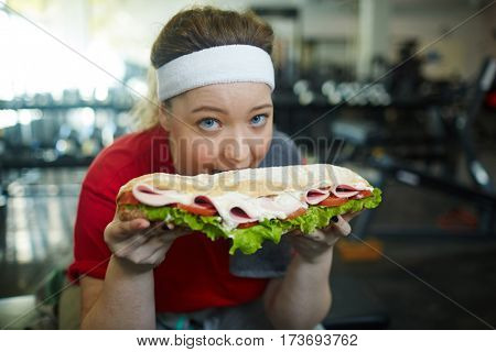 Portrait of cute overweight woman biting into huge fat sandwich while working out in gym, struggling to keep fit