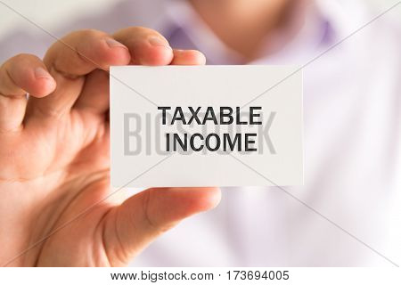 Businessman Holding A Card With Taxable Income Message