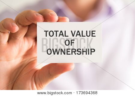 Businessman Holding A Card With Total Value Of Ownership Message