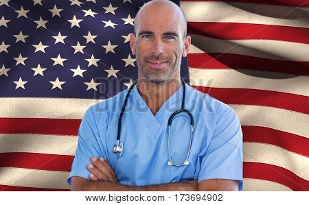 Confident male doctor looking at camera with arms crossed against close-up of american flag