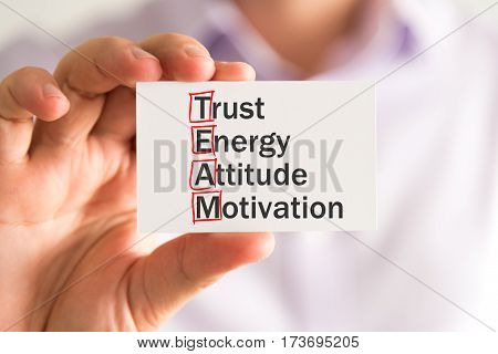 Businessman Holding A Card With Team Trust Energy Attitude Motivation Message