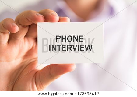 Businessman Holding A Card With Phone Interview Message