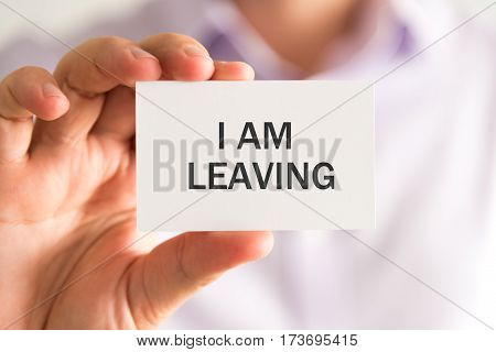 Businessman Holding A Card With I Am Leaving Message