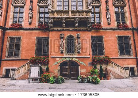 Wroclaw, Silesia, Poland - September, 17th, 2016. Entrance to historic restaurant Piwnica Swidnicka of the Old Town Hall at Wroclaw Market Square. Statues, windows, flower pots and other details.