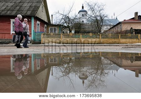Slonim, Belarus - February 21, 2017: Rural Belorussian landscape with old wooden houses reflected in a puddle.