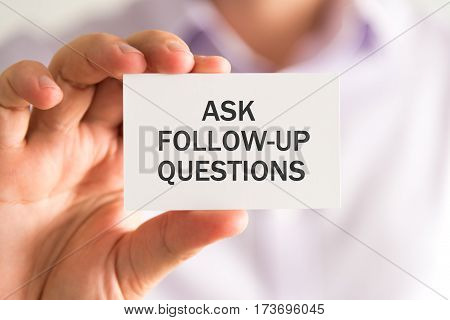 Businessman Holding A Card With Ask Follow-up Questions Message