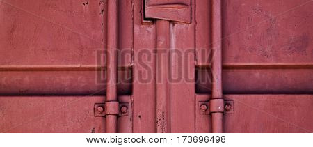 Fragment of a door of the cargo container. Door of the cargo container. Red door.