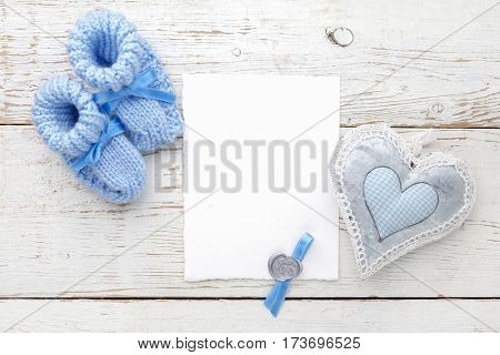 Baby booties with a blank card and heart on a white wooden background
