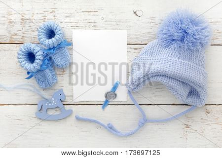 Baby booties with a blank card and cap on a white wooden background