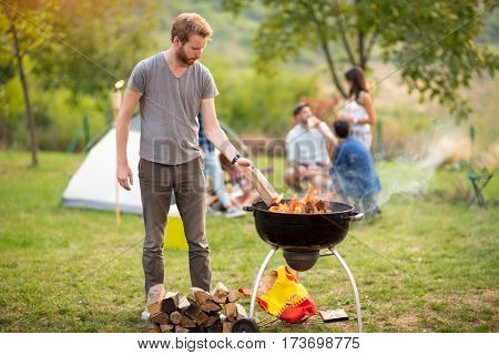 Young man put log in grill fire in campground
