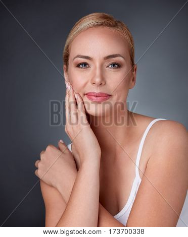 Beautiful middle aged woman smiling looking to the camera touching her cheek, skincare