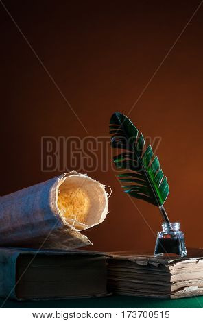 Silhouette of a grren quill pen and a rolled papyrus sheet against a brown background