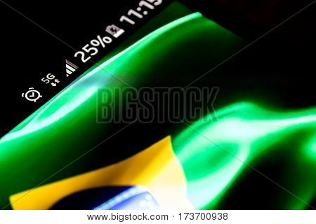Smartphone on wooden background with 5G network sign 25 per cent charge and Brazil flag on the screen.