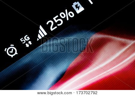Smartphone on wooden background with 5G network sign 25 per cent charge and German flag on the screen.
