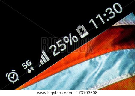 Smartphone on wooden background with 5G network sign 25 per cent charge and USA flag on the screen.