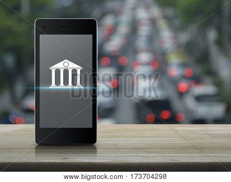 Bank icon on modern smart phone screen over blur of rush hour with cars and road Mobile banking concept