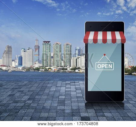 Modern smart mobile phone with on line shopping store graphic and open sign on stone tile floor over office city tower river and blue sky Shop online concept