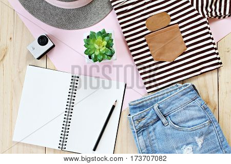 Fashion concept : Lady's outfit with jeans short, blank notebook paper and action camera on wooden background, casual outfit for teenage girls