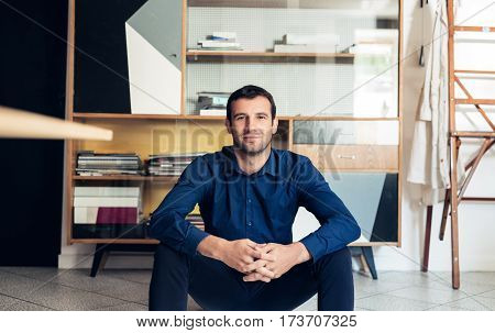 Portrait of a confident and successful young businessman smiling while sitting on the floor in a large work studio