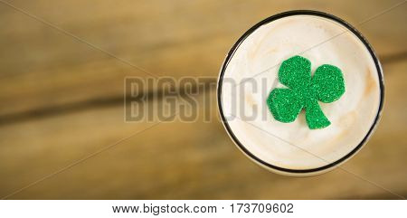 St Patricks Day glass of beer with shamrock on wooden table